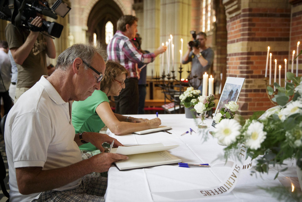 Photo - People sign a condolence register at St. Vitus church in Hilversum, Netherlands, Saturday, July 19, 2014. Three families living in Hilversum were among those killed when a Malaysian jetliner was shot down over Ukraine Thursday. All passengers, 298 people from nearly a dozen nations, more than half being Dutch were killed. Across the Netherlands, at sports clubs, schools and churches, friends met Saturday to console each another and attempt to come to terms with their loss. (AP Photo/Phil Nijhuis)