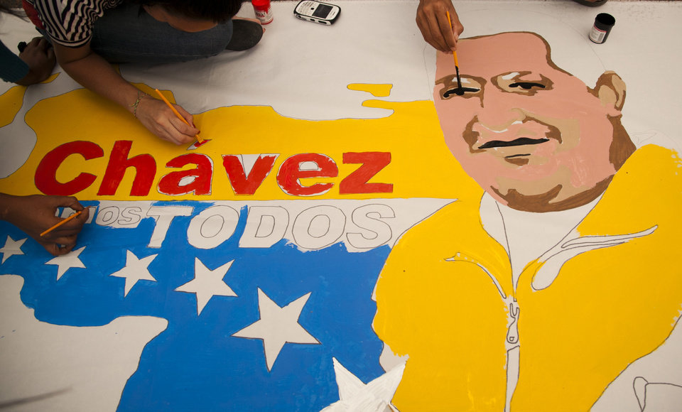 Photo - Supporters of Venezuelan President Hugo Chavez create a poster with his image alongside an outline of their country in Caracas, Venezuela, Friday, Dec. 14, 2012.  Chavez's most influential allies are projecting an image of unity while the president recovers from cancer surgery in Cuba, standing side-by-side and pledging to uphold his socialist movement no matter what happens. (AP Photo/Ariana Cubillos)
