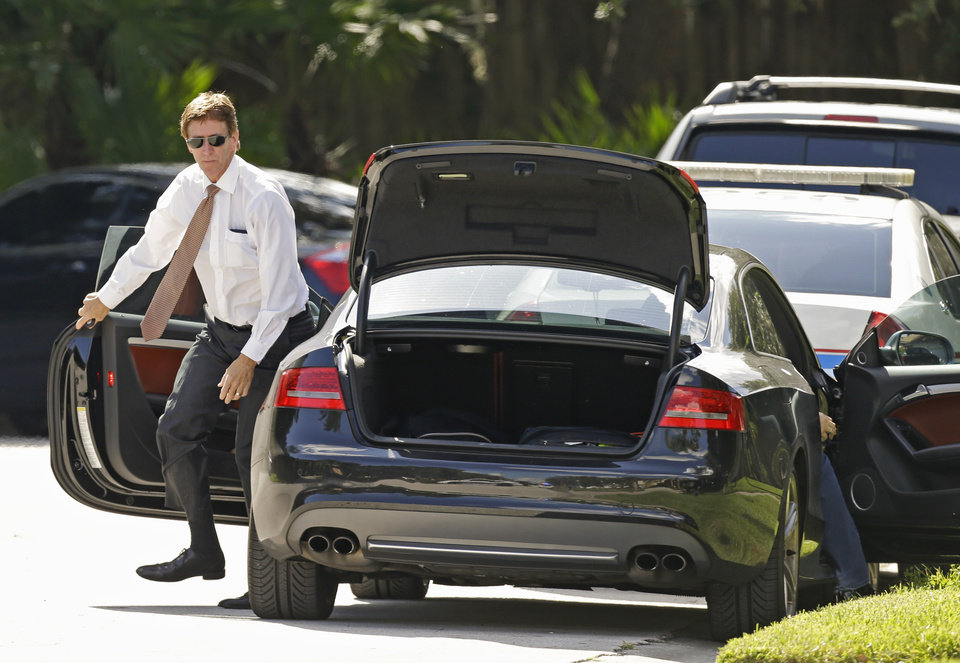 Photo - Mark O'Mara, attorney for George Zimmerman, arrives at the scene of a domestic incident in the Lake Mary, Fla. neighborhood where Zimmerman and his wife Shellie had lived during his murder trial, Monday, Sept. 9, 2013. Zimmerman's wife says on a 911 call that her estranged husband punched her father in the nose, grabbed an iPad out of her hand and smashed it and threatened them both with a gun. Zimmerman was recently found not guilty for the 2012 shooting death of Trayvon Martin. (AP Photo/John Raoux)