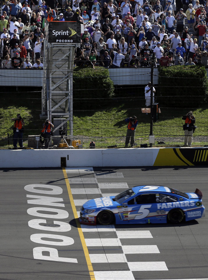 Photo - Kasey Kahne (5) takes the checkered flag to win a NASCAR Sprint Cup Series auto race, Sunday Aug. 4, 2013, at Pocono Raceway in Long Pond, Pa. Jeff Gordon was second. (AP Photo/Mel Evans)