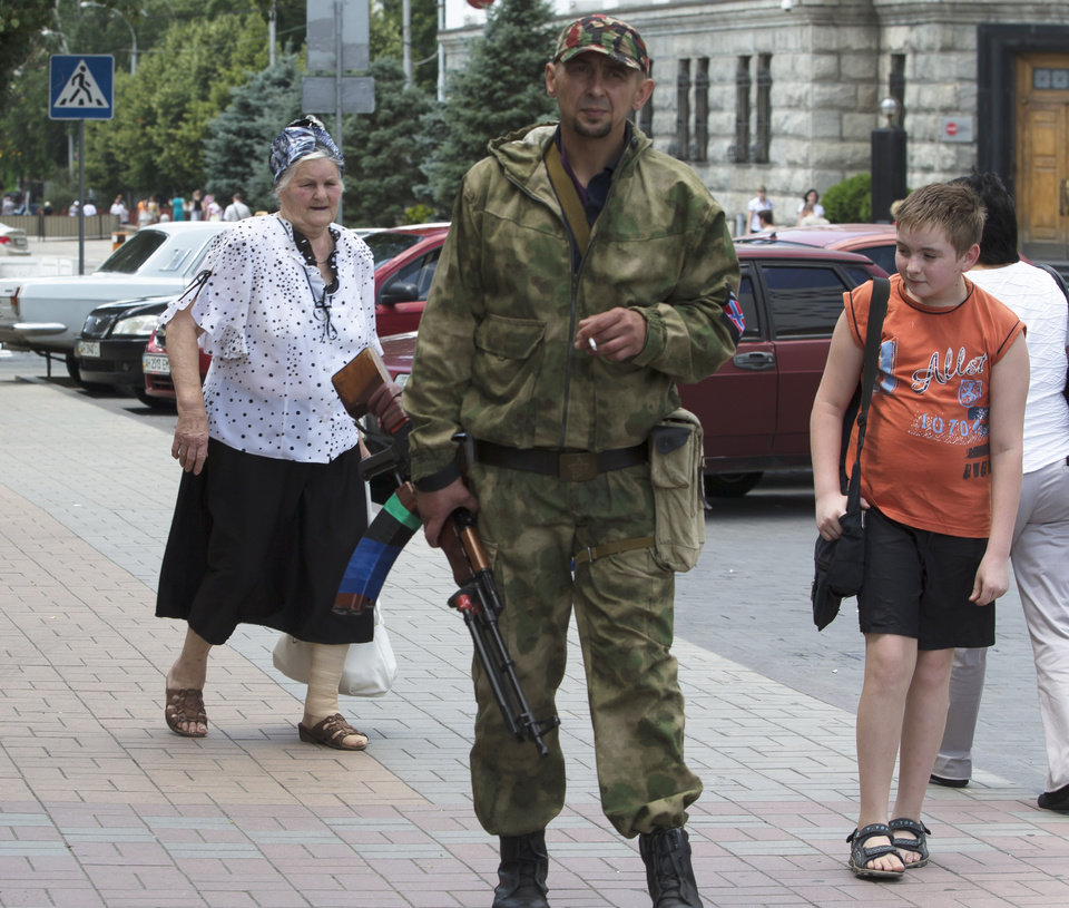 Photo - People walk past a pro-Russian fighter in the city of Donetsk, eastern Ukraine Friday, July 11, 2014. Ukrainian government troops have been fighting for more than three months against separatists in eastern Ukraine. In the last two weeks, however, they have cut the amount of territory held by the rebels in half and forced them out of their stronghold in the city of Slovyansk. The rebels have since regrouped in the eastern city of Donetsk and Ukraine has vowed to cordon the area. (AP Photo/Dmitry Lovetsky)