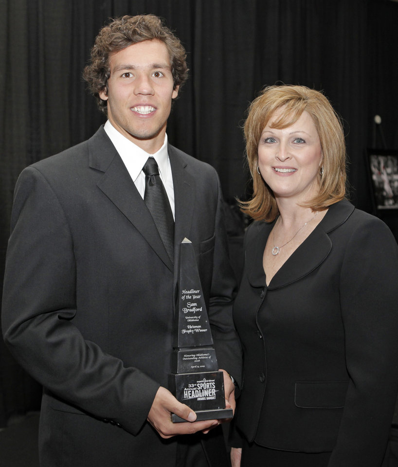Photo - HONOR: University of Oklahoma (OU) quarterback and Headliner of the Year award winner Sam Bradford, left, poses for a photo with March of Dimes state director Laurie Applekamp at the March of Dimes 33rd annual Sports Headliner Awards Banquet at the Skirvin Hilton Hotel in Oklahoma City, Monday, April 13, 2009. Photo by Nate Billings, The Oklahoman ORG XMIT: KOD