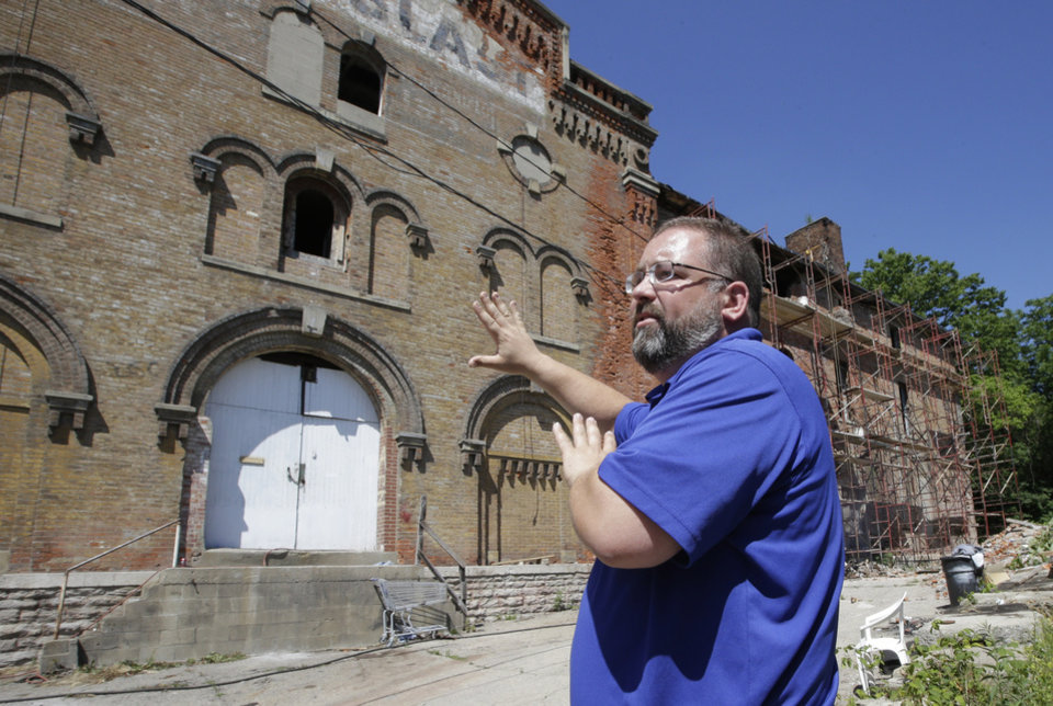 Photo - Steve Hampton, a local architect and the part-time executive director of the nonprofit Brewery District Community Urban Development Corp., stands outside the former Jackson/George Weber Brewing Co., Wednesday, June 19, 2013, that is being renovated in Cincinnati. In the late 19th century, the district was at its peak, with 18 large breweries in operation. (AP Photo/Al Behrman)