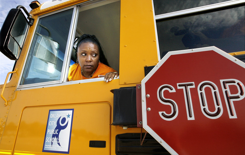 Photo - TRAINER: Tonda Russell is a school bus driver in Oklahoma City since 1982 and she now trains new drivers for the school district. She looks out the driver's window toward the back of her bus as she takes new drivers on a training ride on the streets of the district's transportation center in northeast Oklahoma City, Thursday,  Aug. 7, 2008.   BY JIM BECKEL, THE OKLAHOMAN ORG XMIT: KOD