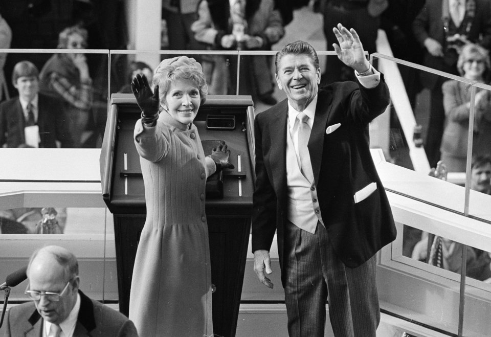 FILE - In this Jan. 20, 1981, file photo, President Ronald Reagan and first lady Nancy Reagan wave to onlookers at the Capitol building as they stand at the podium in Washington following the swearing in ceremony. The inauguration of the U.S. president is traditionally a highly-scripted celebration, with seating charts, schedules, dress rehearsals, and planning committees that map each moment of the history-making day from start to finish. But sometimes the unexpected happens.  It was the first inaugural on the terrace, and the west front has been used ever since. But what happened minutes later made this Inauguration Day different from so many before _ Iran freed 52 American hostages it had held for 444 days. A complicated deal, worked out in the final weeks of the Carter administration, eventually secured their freedom. Reagan, however, announced to the nation that the hostages were on their way home.  (AP Photo, File)