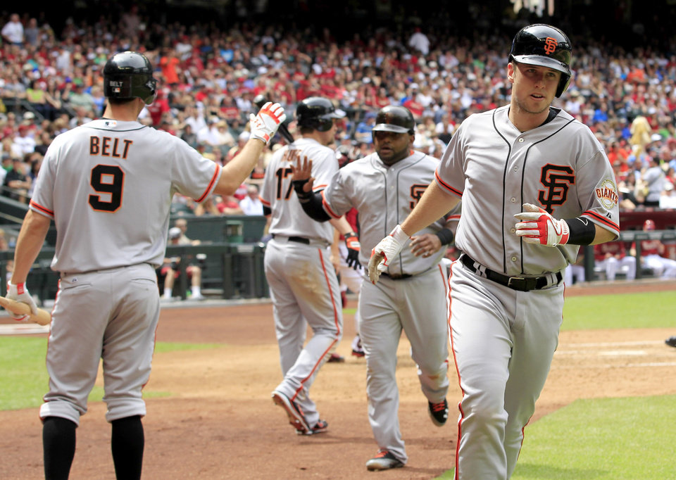 Photo -   San Francisco Giants' Buster Posey, right, runs back to the dugout after celebrating his home run against the Arizona Diamondbacks as teammates Brandon Belt (9), Pablo Sandoval, and Aubrey Huff (17) continue the high-fives during the third inning in an MLB baseball game Sunday, April 8, 2012, in Phoenix.(AP Photo/Ross D. Franklin)
