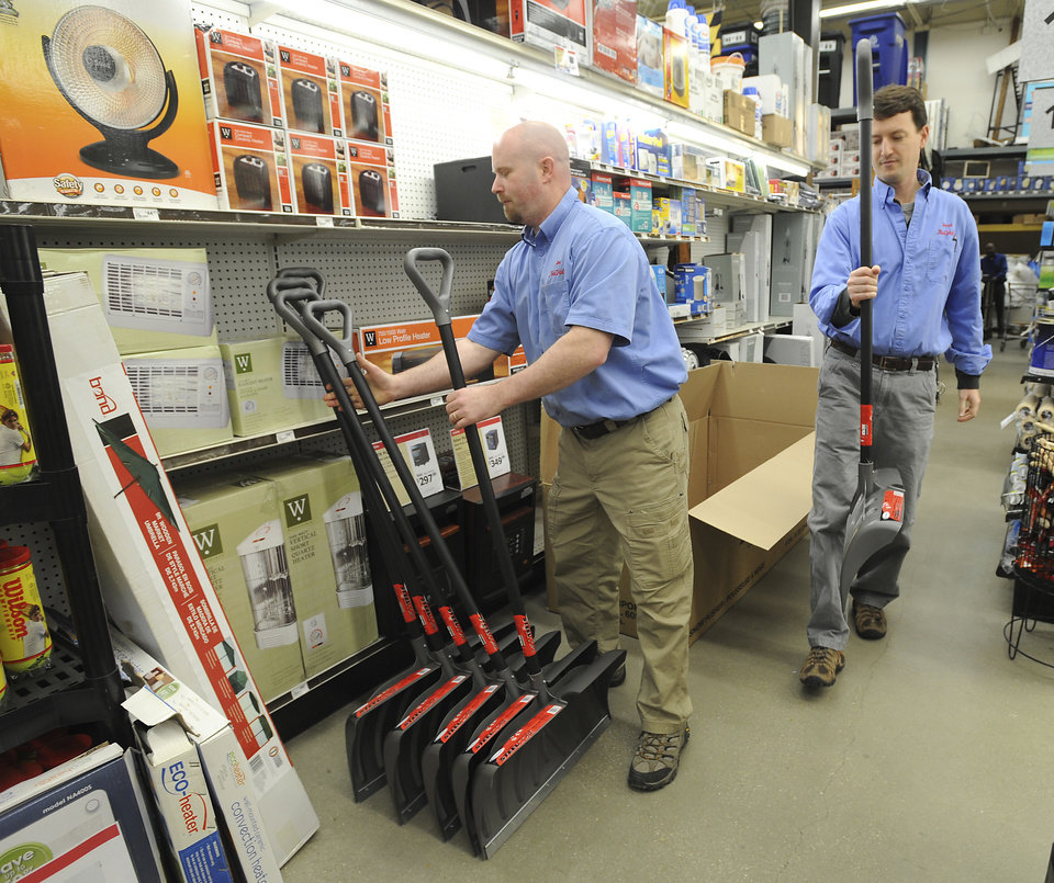 Photo - Store Manager Joe Hogbin, left, and store owner Jared Littmann un-box more snow shovels to bring to the front of the K&B True Value store in Annapolis, Md., Monday, Marh 4, 2013 The coming possibility of a late winter snow storm has people heading to the store, in Bay Ridge, for supplies like snow shovels, window scrapers and ice melt.  (AP Photo/The Capital Gazette,Paul W. Gillespie)