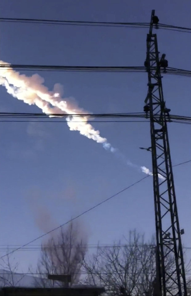 Photo - In this photo taken with a mobile phone camera, a meteorite contrail is seen in Chelyabinsk region on Friday, Feb. 15, 2013. A meteor streaked across the sky of Russia's Ural Mountains on Friday morning, causing sharp explosions and reportedly injuring around 100 people, including many hurt by broken glass. (AP Photo/Sergey Hametov)