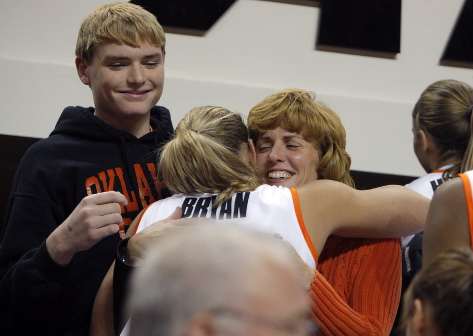 Photo - Oklahoma State's Jenni Bryan (11) greets Brett and Shelley Budke following  the women's college game between Oklahoma State University and Coppin State at Gallagher-Iba Arena in Stillwater, Okla.,  Saturday, Nov. 26, 2011.  Photo by Sarah Phipps, The Oklahoman