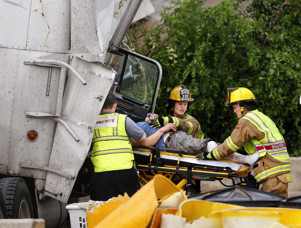 Shawnee firefighters and ambulance personnel carefully remove a driver from the smashed cab of his tractor-trailer after it was lifted from I-40 and dropped onto US 177,  about 20 feet below. A tornado caused extensive damage along I-40 at the junction with  US 177 on the west side of Shawnee Sunday evening,  May 19,  2013.  Photo  by Jim Beckel, The Oklahoman.