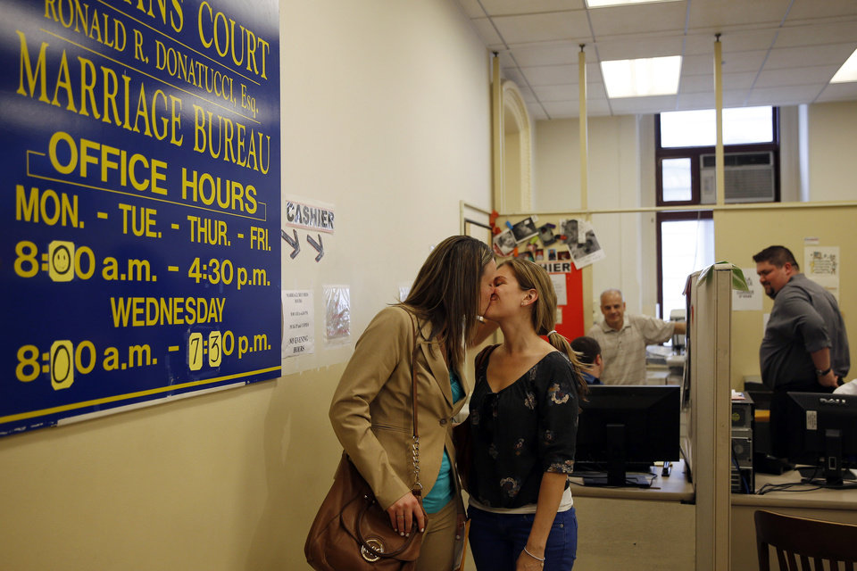 Photo - Ashley Wilson, left, and Lindsay Vandermay, right, both 29, kiss after getting their marriage license at the Philadelphia Marriage Bureau in City Hall, Tuesday, May 20, 2014, in Philadelphia. Pennsylvania's ban on gay marriage was overturned by a federal judge Tuesday. (AP Photo/Matt Slocum)
