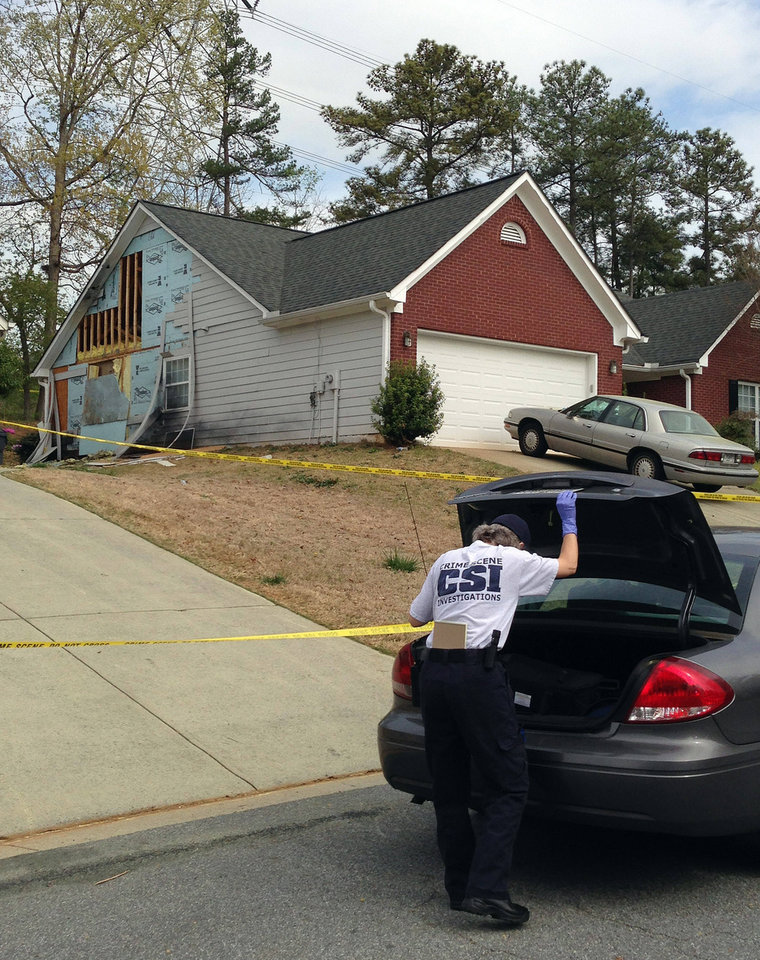An investigator arrives at a damaged home in Suwanee, Ga. on Thursday, April 11, 2013 after Wednesday\'s hostage standoff. A man held four Gwinnett County firefighters hostage for hours before they where freed when police officers stormed the house Wednesday. Authorities said the firefighters encountered an armed man who demanded that his cable and power be turned back on at the house, which was in foreclosure. (AP Photo/Kate Brumback)