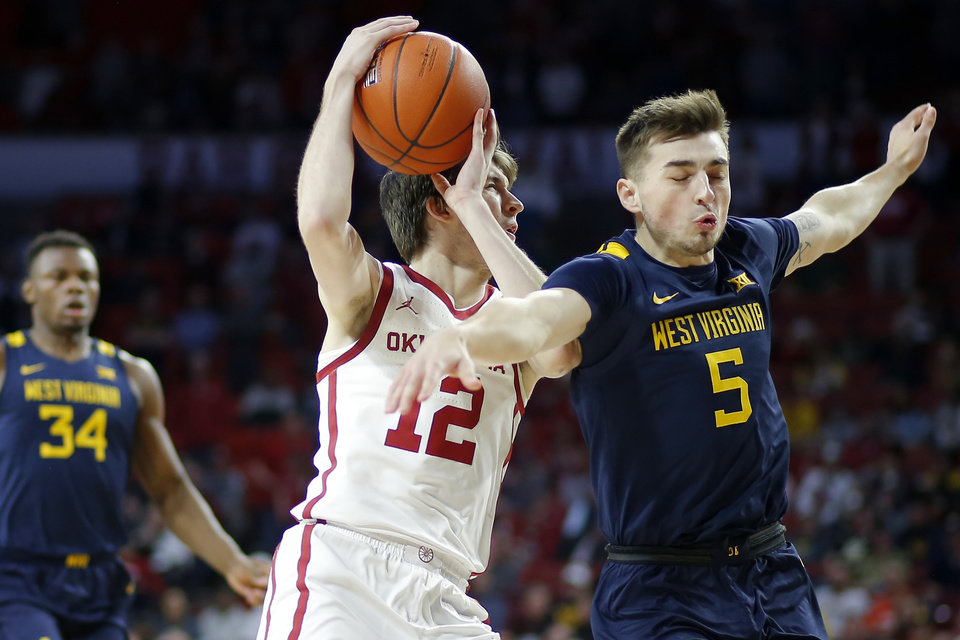 Photo - Oklahoma's Austin Reaves (12) is fouled by West Virginia's Jordan McCabe (5) during an NCAA mens college basketball game between the University of Oklahoma Sooners (OU) and the West Virginia Mountaineers at the Lloyd Noble Center in Norman, Okla.,Saturday, Feb. 8, 2020. Oklahoma won 69-59. [Bryan Terry/The Oklahoman]