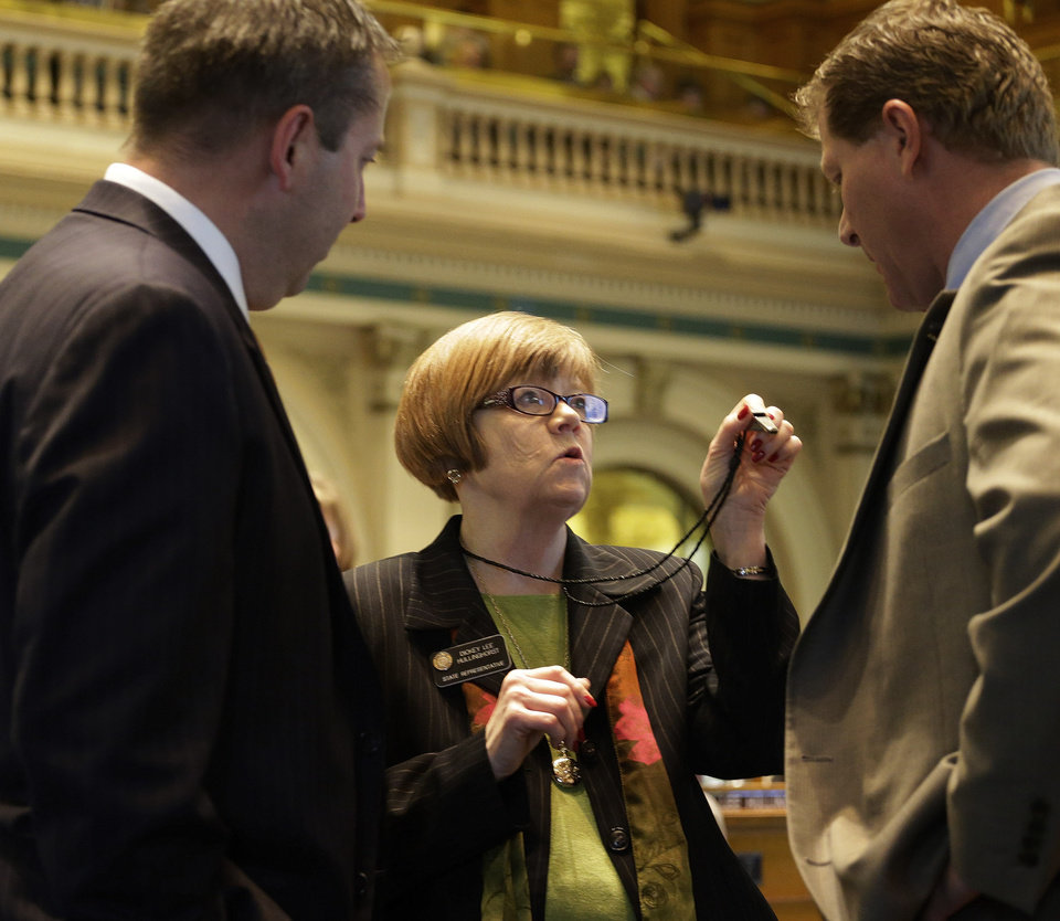 Photo - Rep. Dickey Lee Hullingworst, center, D-Boulder, shows House Minority Leader Mark Waller, left, R-Colorado Springs and Rep. Brian DelGrosso, R-Loveland, her whistle as the debate over gun control bills goes on at the Capitol in Denver on Friday, Feb. 15, 2013. (AP Photo/Ed Andrieski)