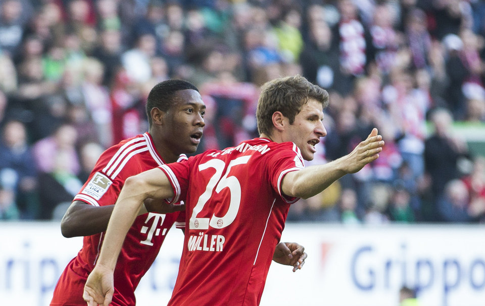 Photo - Bayern's Thomas Mueller, right, celebrates scoring his side's first goal with Bayern's David Alaba of Austria, left,  during the German Bundesliga soccer match between VfL Wolfsburg and Bayern Munich in Wolfsburg, Germany, Saturday, March 8, 2014. (AP Photo/Gero Breloer)