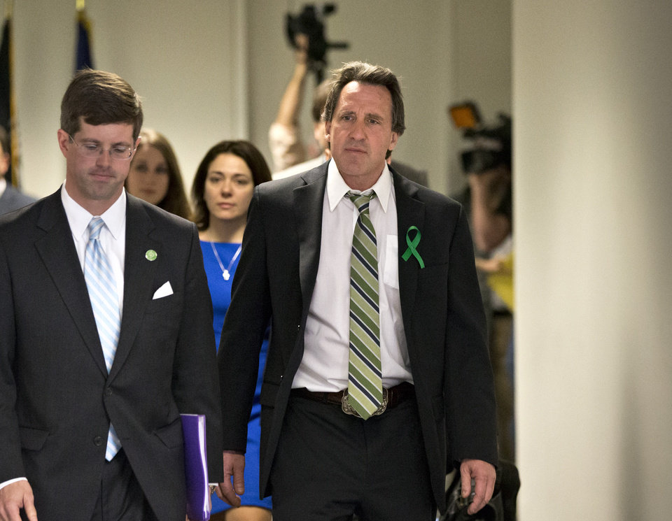 Photo - Neil Heslin, right, whose 6-year-old son Jesse was killed in the mass shooting in Newtown, Conn., arrives with other victims' families to meet privately on Capitol Hill in Washington, Tuesday, April 9, 2013, with Sen. Richard Blumenthal, D-Conn., and Sen. Chris Murphy, D-Conn. Heslin gave moving testimony during a Senate Judiciary Committee hearing in February on the proposed assault weapons ban.  (AP Photo/J. Scott Applewhite)