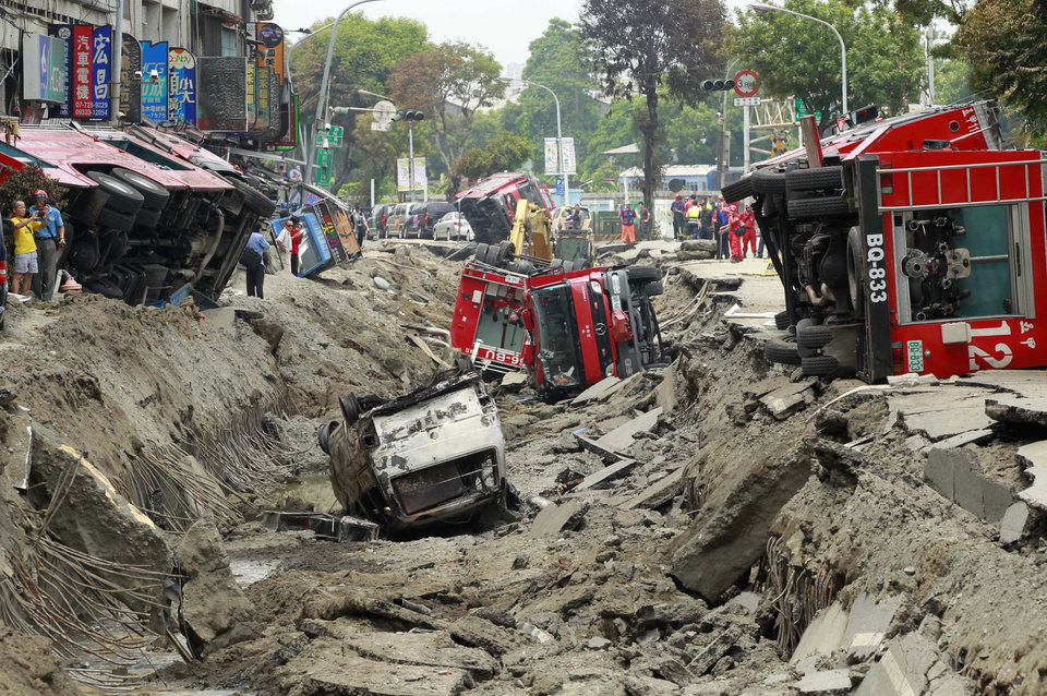 Photo - Damaged vehicles lie in the rubble after massive gas explosions in Kaohsiung, Taiwan, Friday, Aug. 1, 2014. A series of five explosions about midnight Thursday and early Friday ripped through Taiwan's second-largest city, killing scores of people, Taiwan's National Fire Agency said Friday. (AP Photo/Wally Santana)