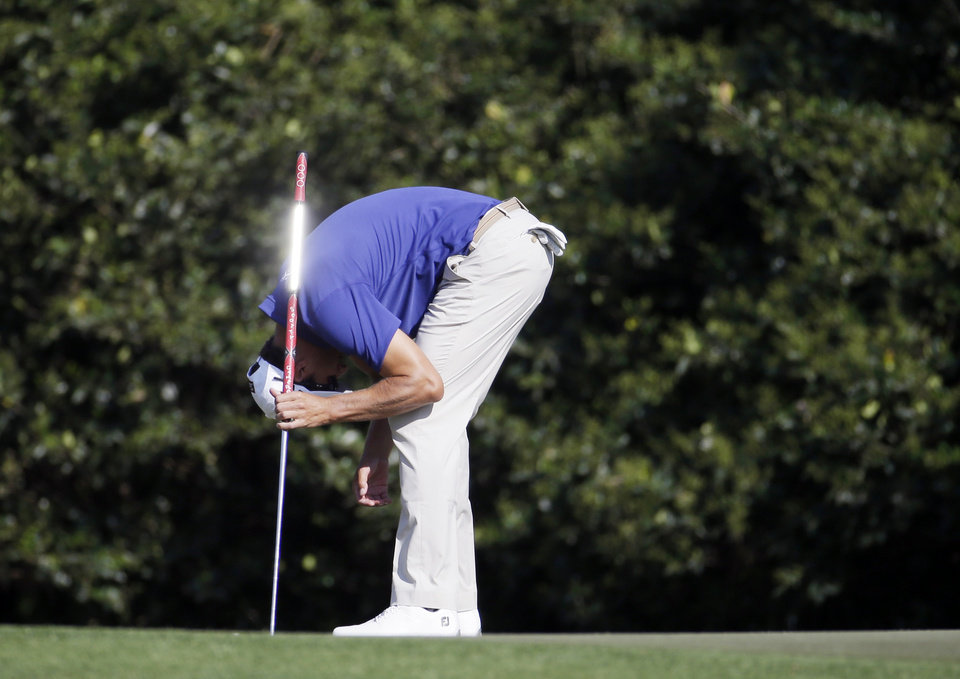 Photo - Adam Scott, of Australia, reacts after missing a birdie putt on the 11th hole during the third round of the Masters golf tournament Saturday, April 12, 2014, in Augusta, Ga. (AP Photo/Darron Cummings)