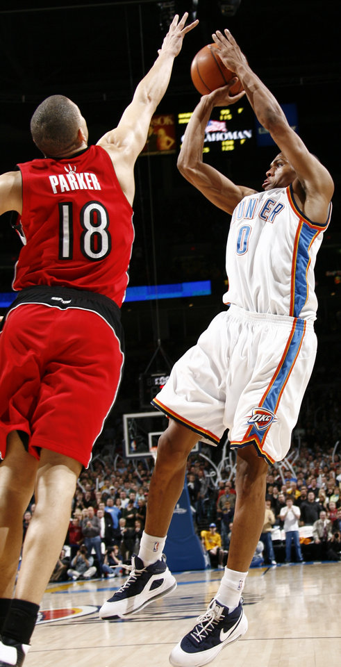 Photo - Oklahoma City's Russell Westbrook takes a shot past Anthony Parker of Toronto in the second half of the NBA basketball game between the Toronto Raptors and the Oklahoma City Thunder at the Ford Center in Oklahoma City, Friday, Dec. 19, 2008. The Thunder won, 91-83. BY NATE BILLINGS, THE OKLAHOMAN