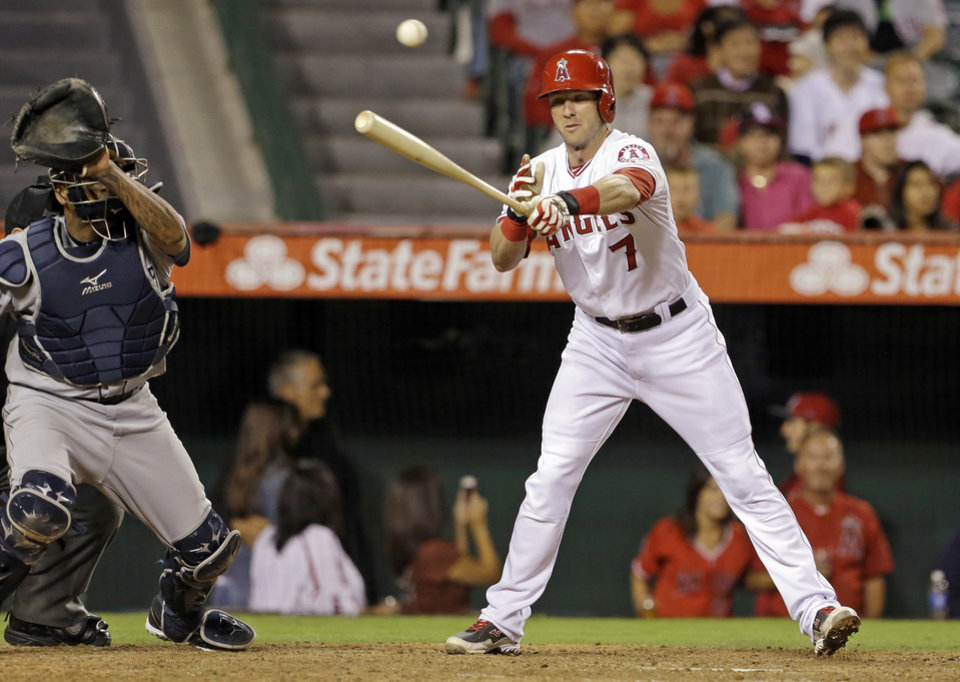 Photo - Los Angeles Angels' Andrew Romine misses for a strike as the ball sails over Seattle Mariners catcher Henry Blanco, allowing Collin Cowgill to steal home, in the seventh inning of a baseball game in Anaheim, Calif., Saturday, Sept. 21, 2013. (AP Photo/Reed Saxon)