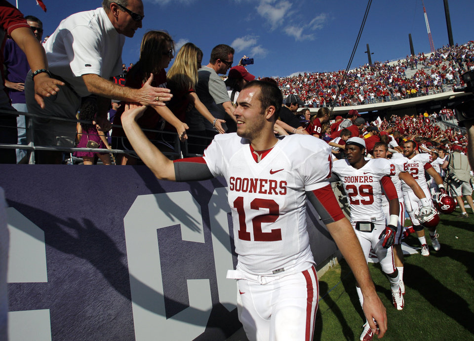 Photo - Oklahoma's Landry Jones (12) leads the team as they celebrate with fans following their NCAA college football game against TCU Saturday, Dec. 1, 2012, in Fort Worth, Texas. Oklahoma won 24-17. (AP Photo/Tony Gutierrez)