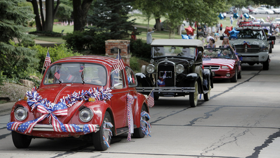 A 1970 VW Beetle driven by Tom Roger with his wife, Holli Roger, and daughter, Faith Roger, 5, as passengers leads a line of cars in the Quail Creek Fourth of July parade along Quail Creek Road in Oklahoma City, Saturday, July 4, 2009. Photo by Nate Billings, The Oklahoman