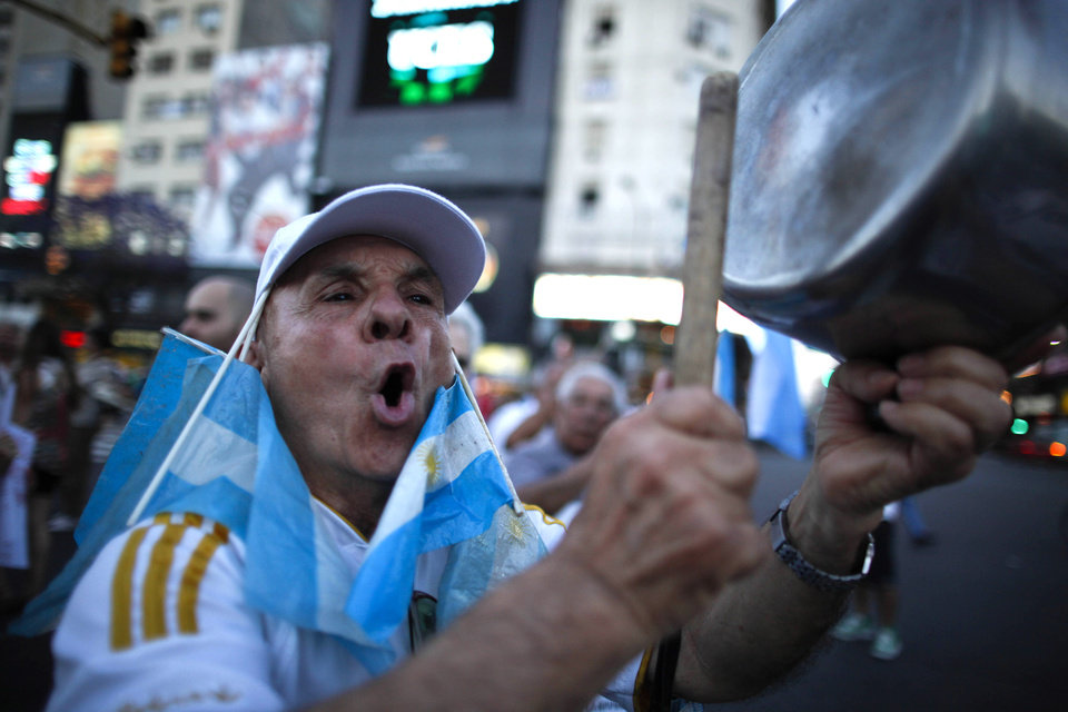 Photo -   A protester bangs a pot during a march against Argentina's President Cristina Fernandez in Buenos Aires, Argentina, Thursday, Nov. 8, 2012. Angered by rising inflation, violent crime and high-profile corruption, and afraid Fernandez will try to hold onto power indefinitely by ending constitutional term limits, the protesters banged pots and marched on the iconic obelisk in Argentina's capital. Protests also were held in plazas nationwide and outside Argentine embassies and consulates around the world. (AP Photo/Natacha Pisarenko)