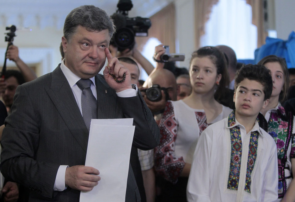 Photo - Ukrainian presidential candidate Petro Poroshenko,  left, casts his ballot as his daughter Eugenia, son Mykhailo and daughter Alexandra look on at a polling station during the presidential election in Kiev, Ukraine, Sunday, May 25, 2014. Ukraine's critical presidential election got underway Sunday under the wary scrutiny of a world eager for stability in a country rocked by a deadly uprising in the east.(AP Photo/Sergei Chuzavkov)