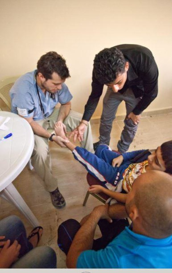Photo -  Dr. Emanuel Dolph examines a young boy's leg at a clinic in Iraq.   Whittenburger, Valerie -  Photo Provided