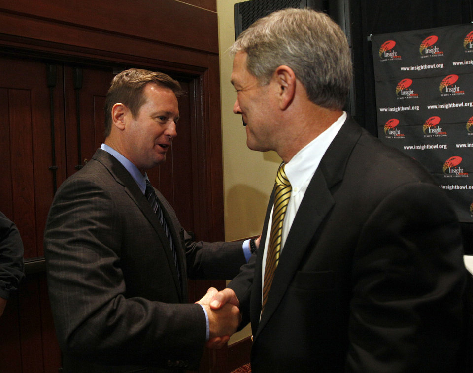 Photo - Iowa head coach Kirk Ferentz and Oklahoma head coach Bob Stoops greet each other during a press conference for the Insight Bowl at the Camelback Inn in Paradise Valley, Ariz.,  Thursday, Dec. 29, 2011. Photo by Sarah Phipps, The Oklahoman