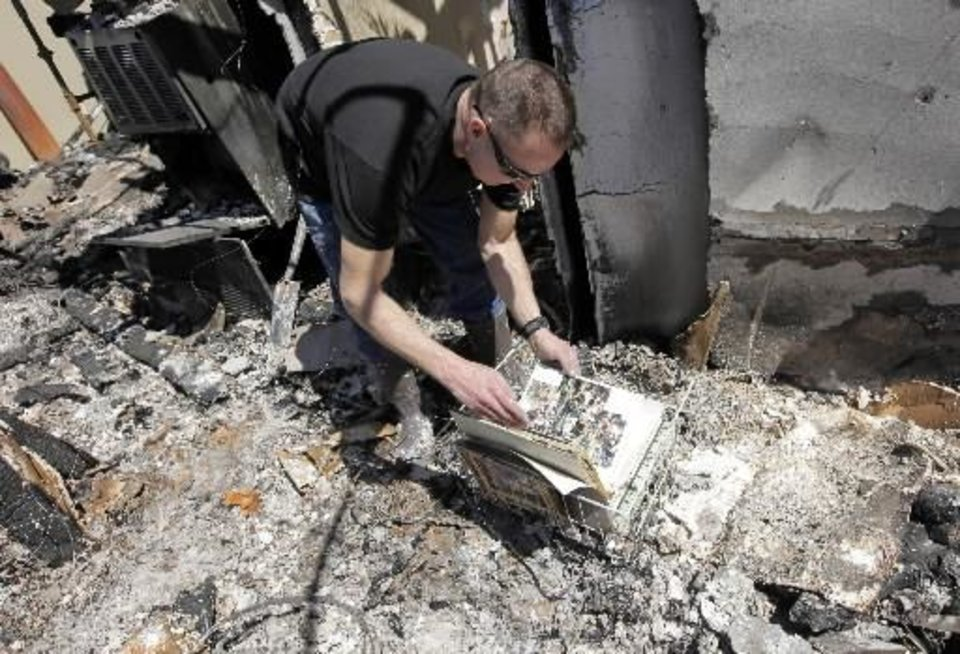 Todd Sewell looks through an album of pictures that managed to survive the  fire which destroyed his home at 11533 Berkshire Court in  Midwest  City, Okla., Saturday, April 11, 2009. Wildfires struck the area on Thursday, April 9, 2009, destroying several homes. Photo by Nate Billings