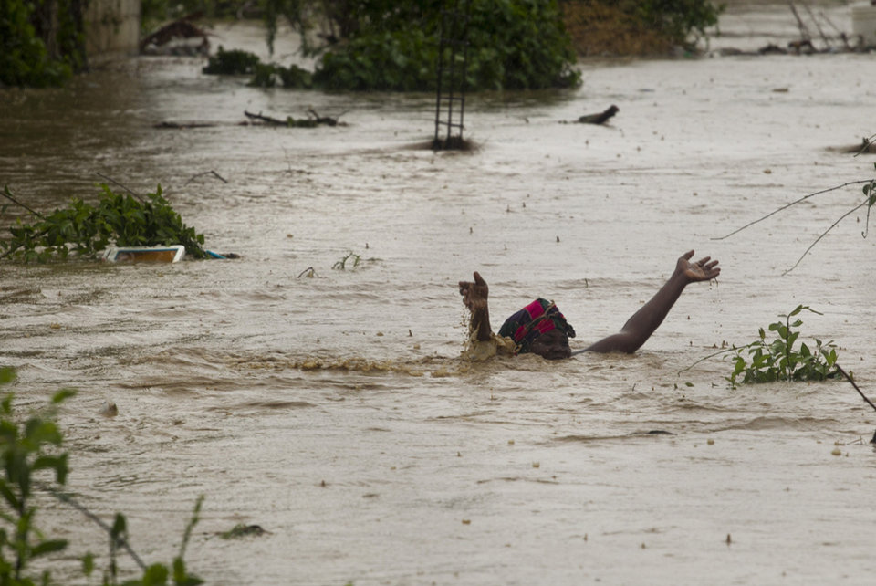 Photo -   In this photo released by the U.N. mission in Haiti, MINUSTAH, a woman swims through flood waters in a low lying area affected by Tropical Storm Isaac in Port-au-Prince, Haiti, Saturday, Aug. 25, 2012. Tropical Storm Isaac swept across Haiti's southern peninsula early Saturday, dousing a capital city prone to flooding and adding to the misery of a poor nation still trying to recover from the 2010 earthquake. (AP Photo/MINUSTAH, Logan Abassi)