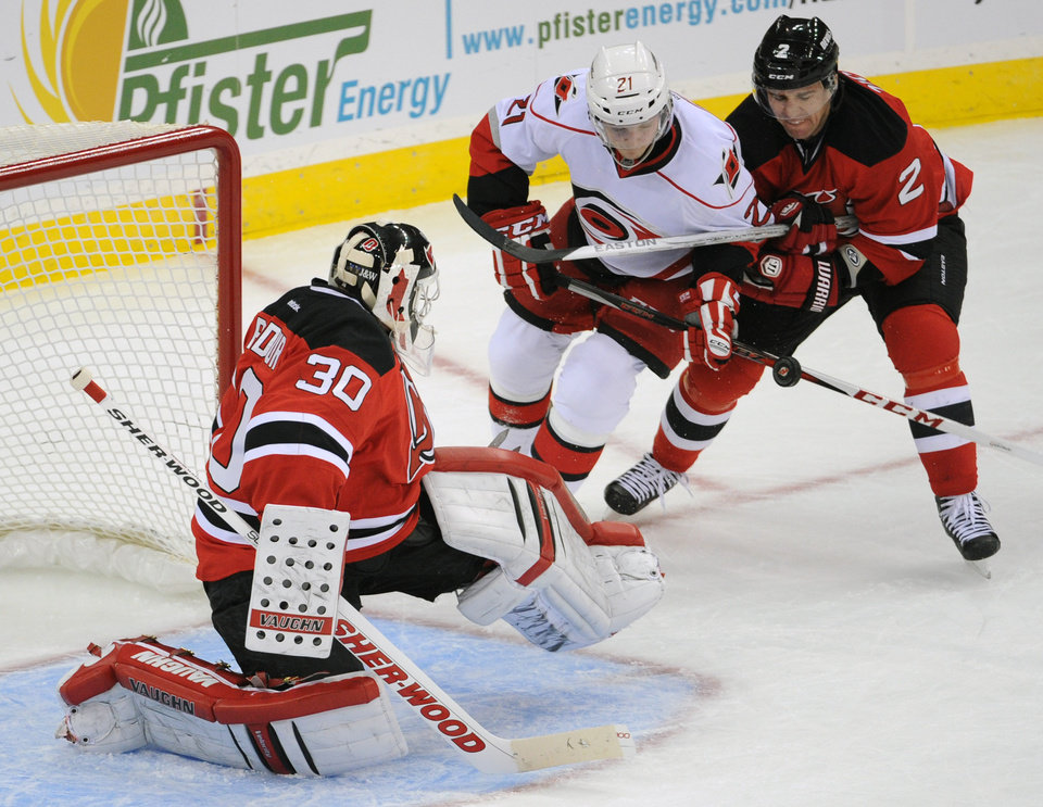 New Jersey Devils' Marek Zidlicky, right, of the Czech Republic, ties up Carolina Hurricanes' Drayson Bowman as Devils goaltender Martin Brodeur makes a save during the first period of an NHL hockey game Tuesday, Feb. 12, 2013, in Newark, N.J. (AP Photo/Bill Kostroun)