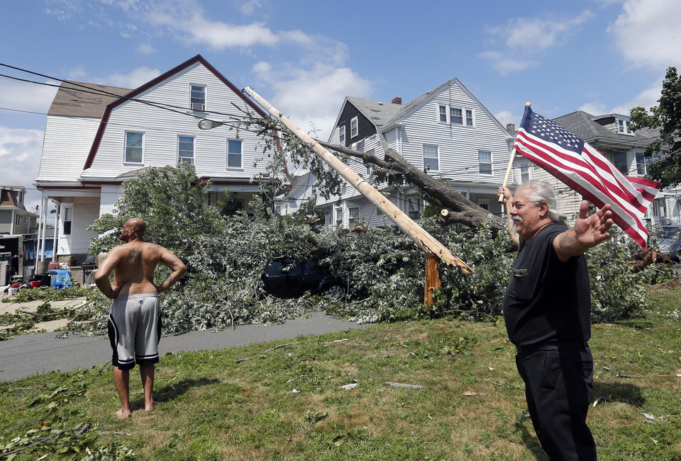 Photo - Homeowner Lenny DiBartolomeo, right, waves a flag as he and his tenant Wayne Devaughn, left, observe damage to their house in Revere, Mass., Monday, July 28, 2014 after a tornado touched down. Both men said they were grateful that they knew of no injuries. (AP Photo/Elise Amendola)