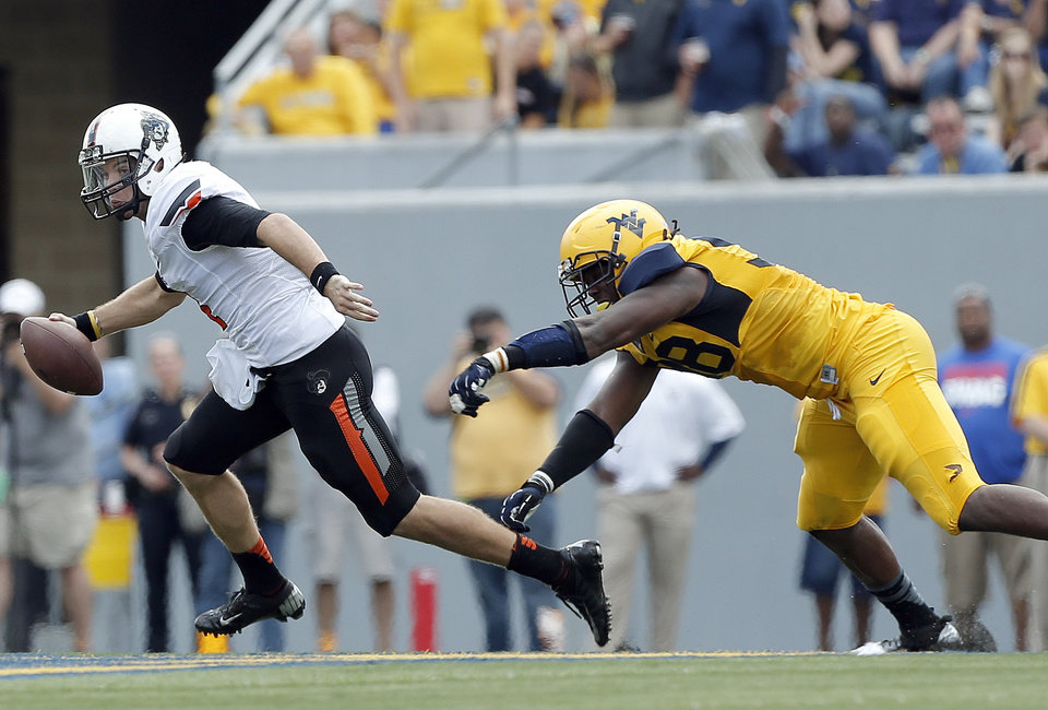 Photo - Oklahoma State's J.W. Walsh (4) scrambles as West Virginia's Shane Commodore (38) chases him down during a college football game between the Oklahoma State University and West Virginia University on Mountaineer Field at Milan Puskar Stadium in Morgantown, W. Va.,   Saturday, Sept. 28, 2013. Photo by Sarah Phipps, The Oklahoman