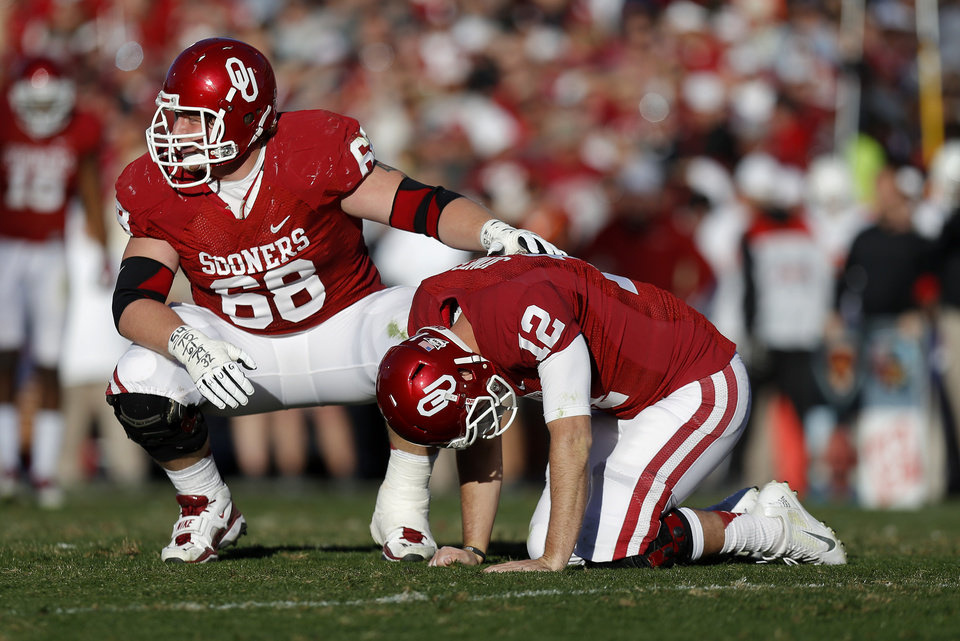 Photo - Oklahoma's Landry Jones (12) is slow to get up beside Oklahoma's Bronson Irwin (68) during the Bedlam college football game between the University of Oklahoma Sooners (OU) and the Oklahoma State University Cowboys (OSU) at Gaylord Family-Oklahoma Memorial Stadium in Norman, Okla., Saturday, Nov. 24, 2012. Oklahoma won 51-48. Photo by Bryan Terry, The Oklahoman