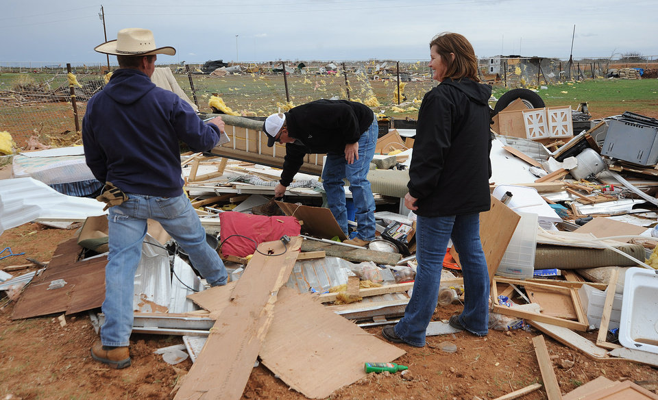 People search through debris after a storm passed through Gardendale, Texas early Monday, March 19, 2012. The storm overturned a trailer, hospitalizing one man and causing damage to several houses, vehicles and other structures in the area. Gardendale is a rural community about 8 miles north of Odessa. The forecast for northern Texas and southeast Oklahoma calls for baseball-sized hail, damaging winds and possibly tornadoes, according to the National Weather Service's Storm Prediction Center in Norman, Okla. (AP Photo/The Odessa American, Mark Sterkel)