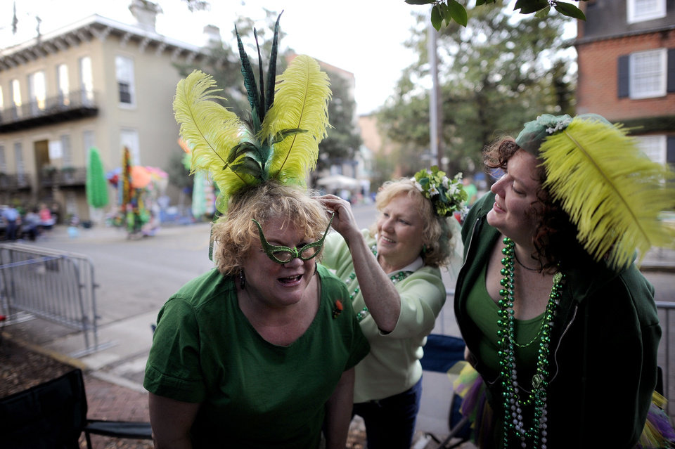 Photo - Bev Kehayes, left, of Greensboro, N.C., gets her homemade hat pinned on her head by her friend Mary Parrish, center, and Sara Farnsworth, right, before Savannah's 189-year-old St. Patrick's Day parade, Saturday, March 16, 2013, in Savannah, Ga. St. Patrick's Day falls on March 17, which is Sunday. But a number of cities, including Savannah, New York and Chicago are all holding parades Saturday to take advantage of the full weekend. (AP Photo/Stephen Morton)