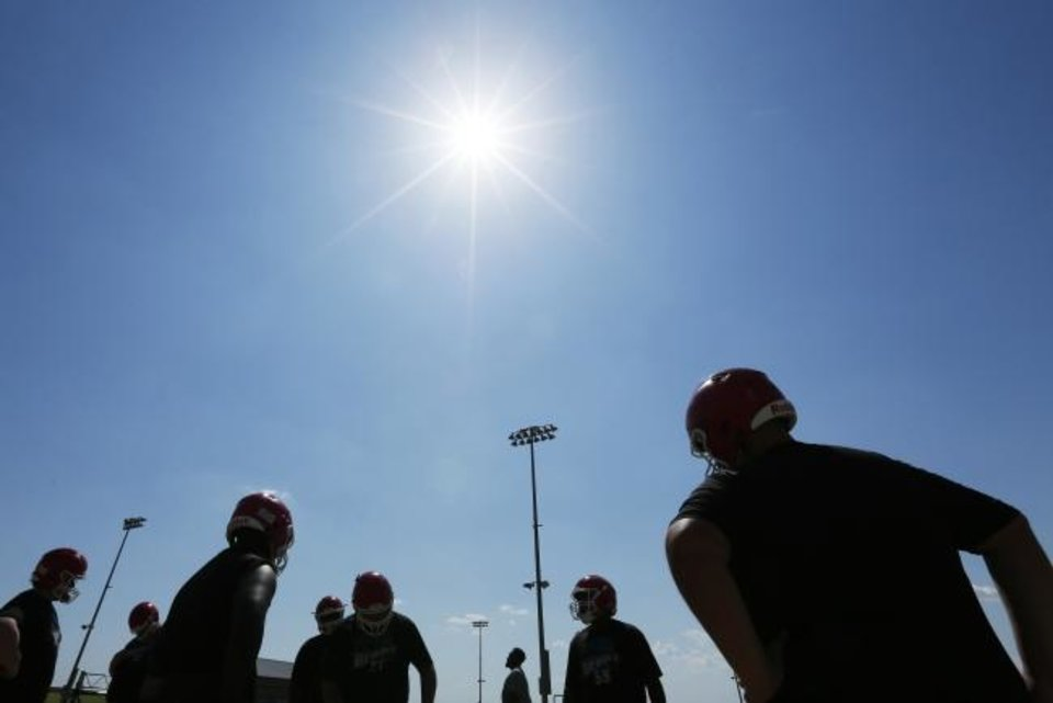 Photo -  Players are silhouetted as they stand in the heat between drills Monday during high school football practice for the John Marshall Bears. [Nate Billings/The Oklahoman]