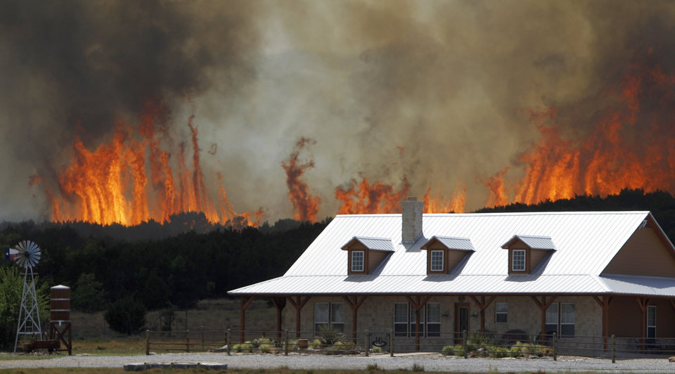 Photo - FILE - In this April 19, 2011 file photo, a wildfire threatens a house near Possum Kingdom, Texas. Global warming is rapidly turning America the beautiful into America the stormy, sneezy and dangerous, according to a new federal scientific report released Tuesday, May 6, 2014.  The report emphasizes how warming and its all-too-wild weather are changing daily lives, even using the phrase