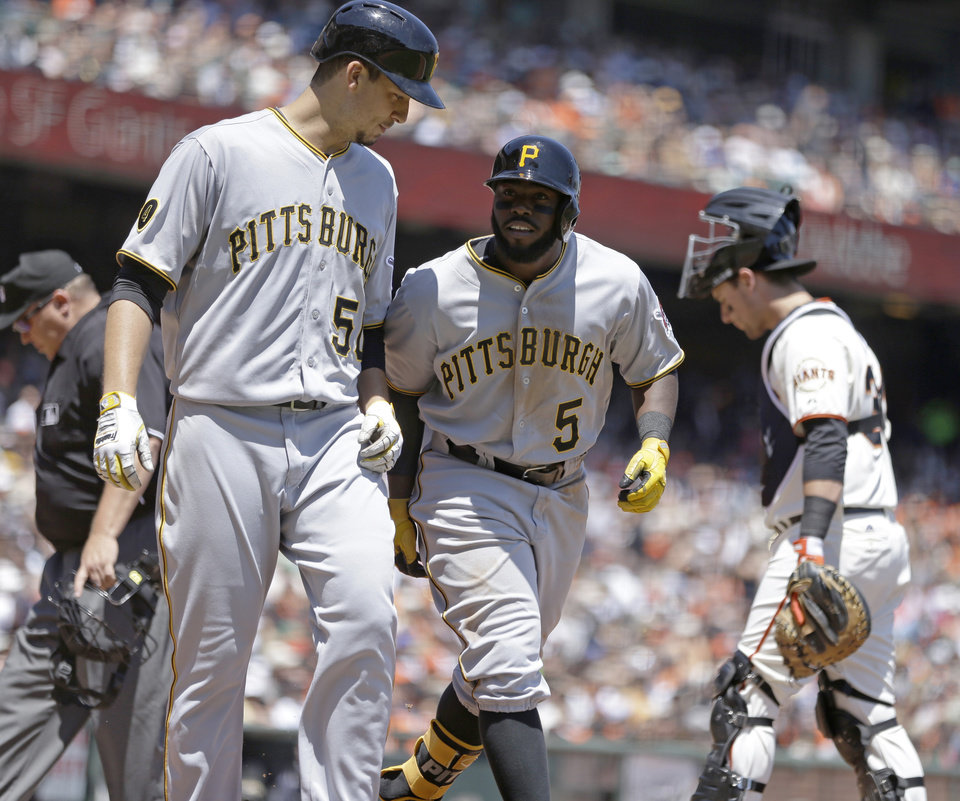 Photo - Pittsburgh Pirates' Josh Harrison (5) and Charlie Morton (50) celebrate Harrison's two run home run hit off San Francisco Giants' Tim Lincecum in the third inning of a baseball game Wednesday, July 30, 2014, in San Francisco. (AP Photo/Ben Margot)