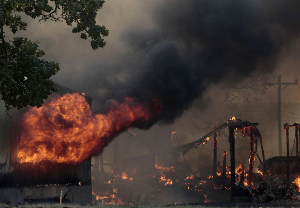 Photo - A mobile home burns at South Cedar and South 8th St.,  in Luther, Okla.,  during a large wildfire, Friday, Aug. 3, 2012. Photo by Sarah Phipps, The Oklahoman