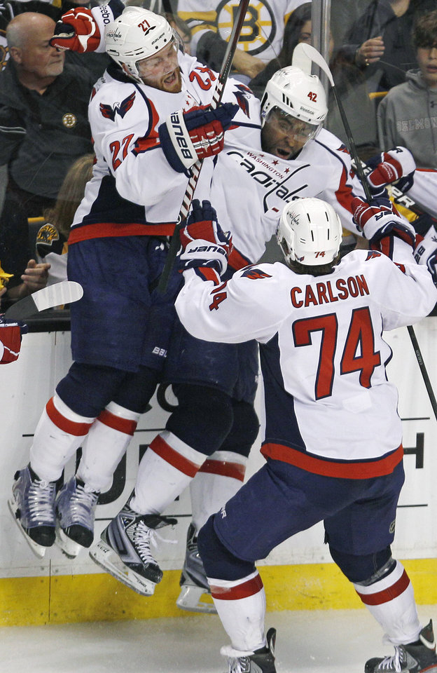 Photo -   Washington Capitals right wing Joel Ward, center, is congratulated by teammates after his goal against the Boston Bruins during overtime of Game 7 of an NHL hockey Stanley Cup first-round playoff series, in Boston on Wednesday, April 25, 2012. The Capitals won 2-1. From left with Ward are Karl Alzner and John Carlson. (AP Photo/Charles Krupa)