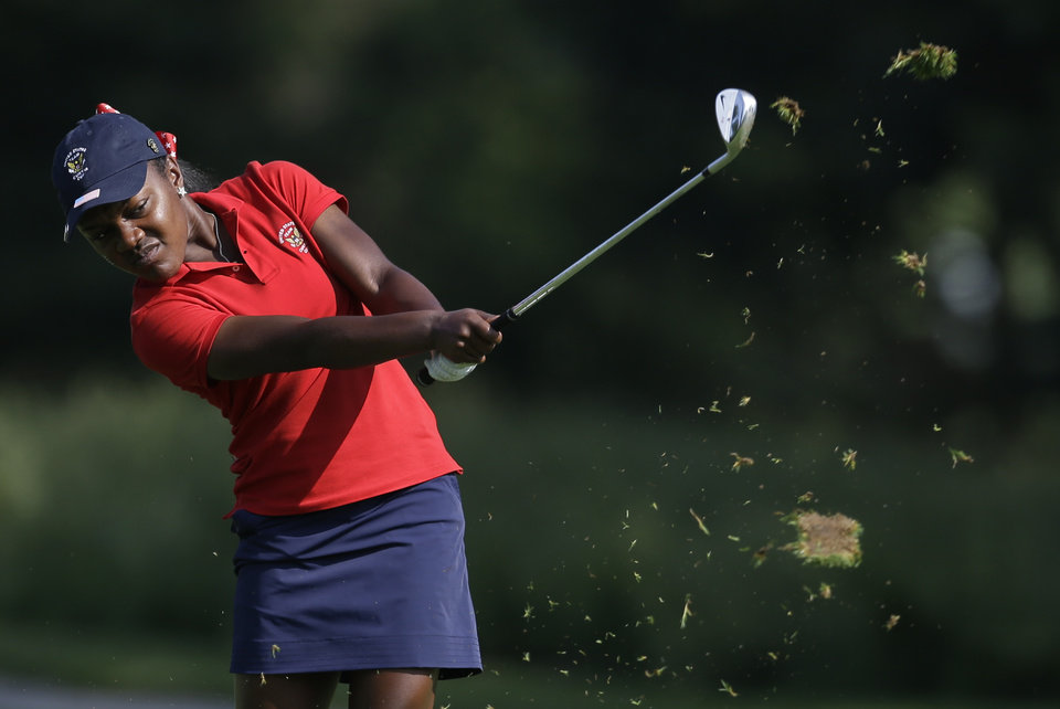 Photo - United States' Mariah Stackhouse hits her approach shot to the fifth green during the 38th Curtis Cup amateur golf match against Great Britain and Ireland Friday, June 6, 2014, in St. Louis. (AP Photo/Jeff Roberson)