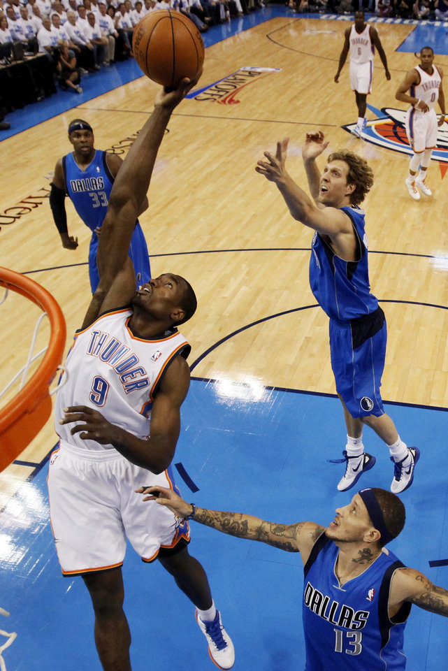 Oklahoma City\'s Serge Ibaka (9) grabs a rebound between Dallas\' Brendan Haywood (33), Dirk Nowitzki (41) and Delonte West (13) during Game 2 of the first round in the NBA basketball playoffs between the Oklahoma City Thunder and the Dallas Mavericks at Chesapeake Energy Arena in Oklahoma City, Monday, April 30, 2012. Photo by Nate Billings, The Oklahoman
