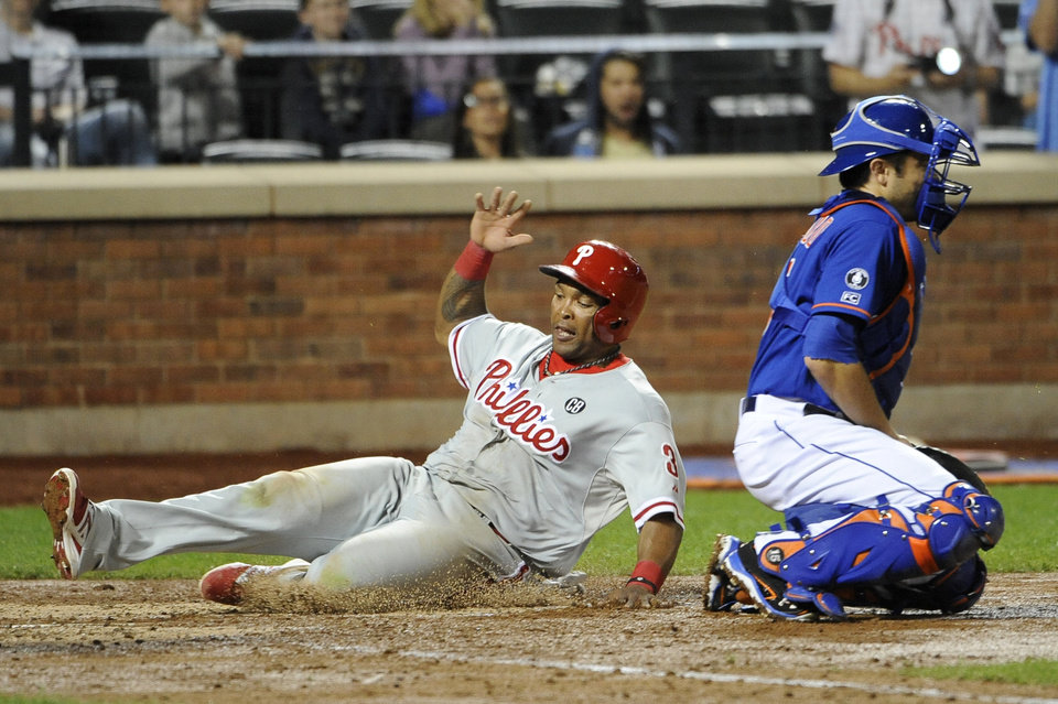 Photo - Philadelphia Phillies' Marlon Byrd, left, scores at home plate behind New York Mets catcher Travis d'Arnaud on a single by Cody Asche in the seventh inning of a baseball game at Citi Field, Friday, Aug. 29, 2014, in New York. (AP Photo/Kathy Kmonicek)