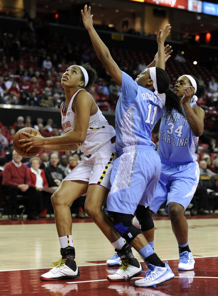 Maryland's Tianna Hawkins , left, looks to shoot as North Carolina's Brittany Roundtree, center, defends during the first half of an NCAA college basketball game on Thursday, Jan. 24, 2013, in College Park, Md. North Carolina's Xylina McDaniel, right, watches the play. (AP Photo/Gail Burton).