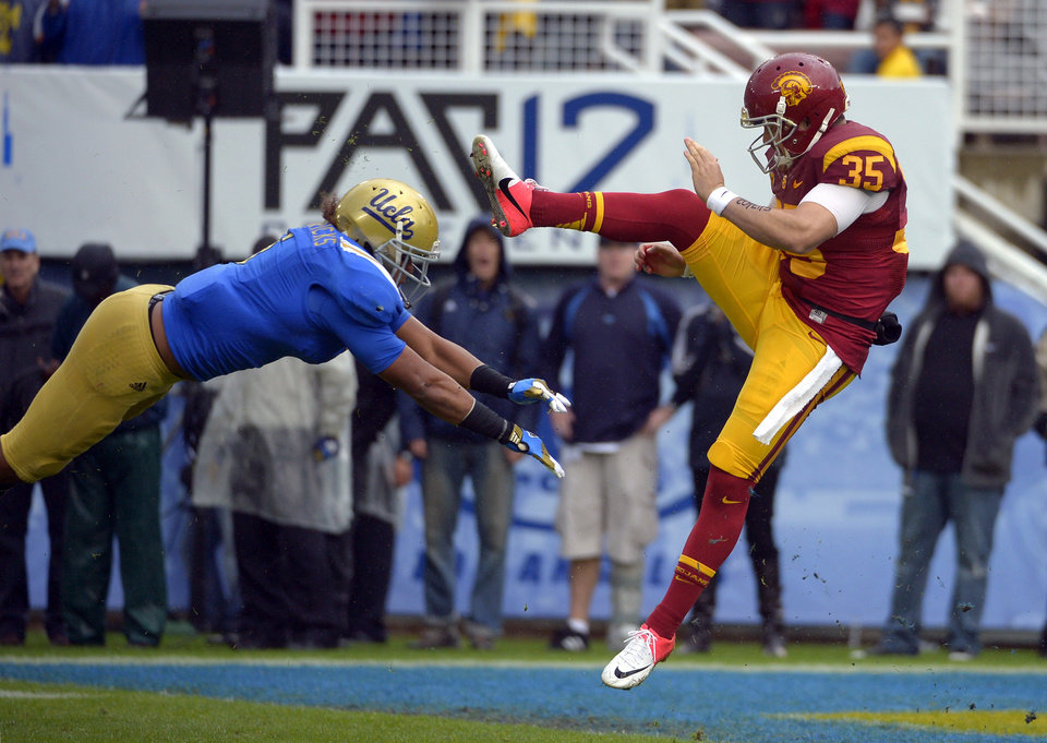 UCLA linebacker Eric Kendricks, left, blocks a punt by Southern California's Kris Albarado during the second half of their NCAA college football game, Saturday, Nov. 17, 2012, in Pasadena, Calif. UCLA won 38-28. (AP Photo/Mark J. Terrill)