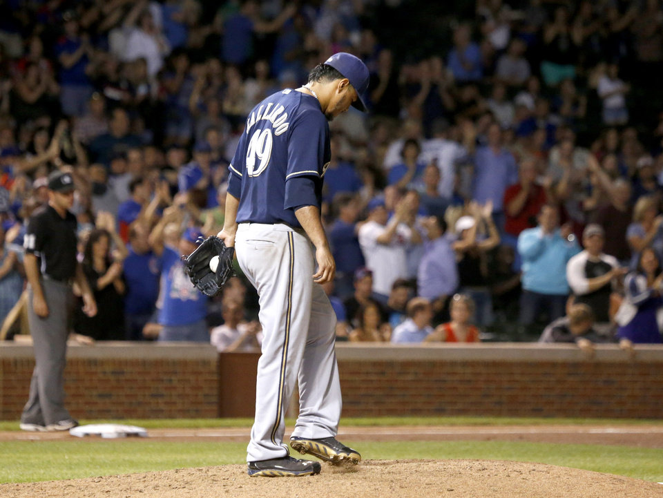 Photo - Milwaukee Brewers starting pitcher Yovani Gallardo returns to the mound after giving up a two-run home run to Chicago Cubs' Arismendy Alcantara, also scoring Welington Castillo, during the fifth inning of a baseball game Tuesday, Sept. 2, 2014, in Chicago. (AP Photo/Charles Rex Arbogast)