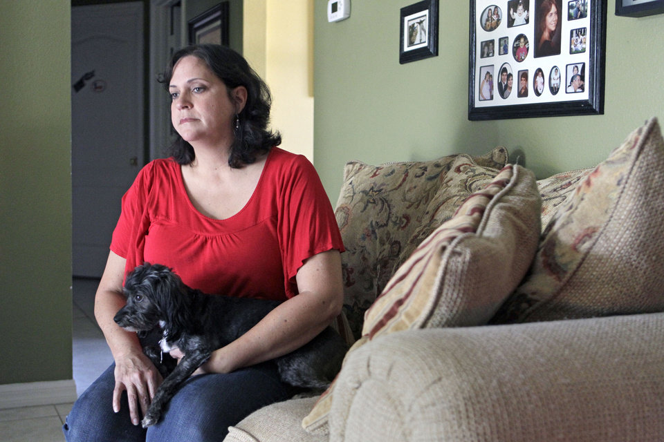 Photo -   In this Tuesday, July 31, 2012 photo, Marisol Walker sits with her dog in her home in Ocoee, Fla. Walker is fighting to keep the home that she and he husband bought about a year before his business collapsed. Walker says they haven't been able to pay the mortgage in 1½ years. She works part-time, while her husband is trying to restart his business. She finds the current political debate alienating.